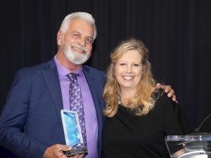 Dennis Brown receiving the Humanitarian award from Daphne Barlow Stigliano